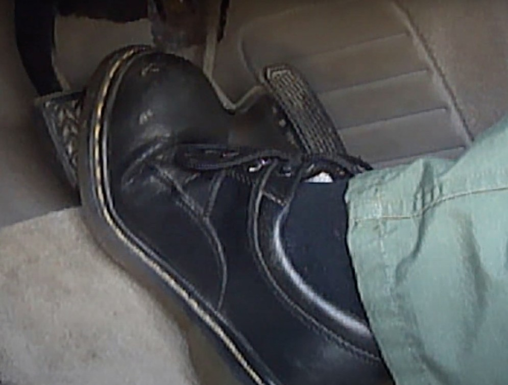 Photo of foot pressing down on brake pedal that goes to the floorboard, indicating brake servicing is needed.